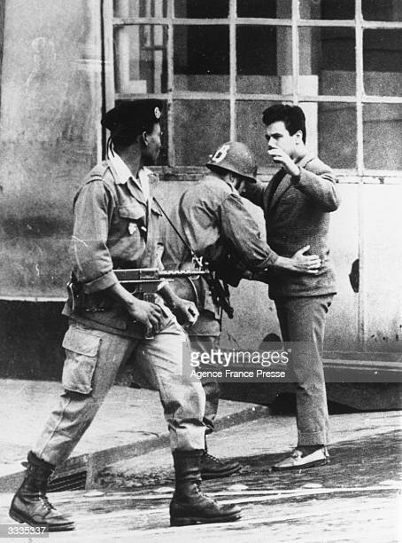 French soldiers search a civilian in an Algiers street during the Algerian War of Independence