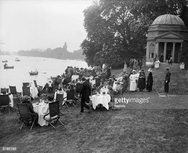 People having tea beside the boating lake at the New Garrick Lawn Club Hampton Court