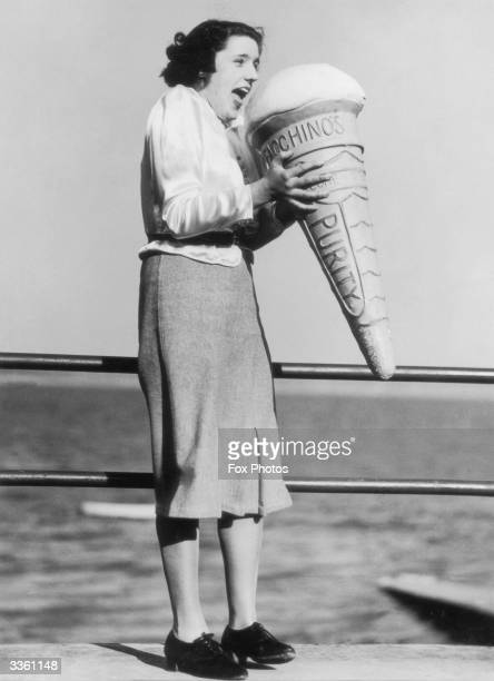 A woman holding a giant model of an ice cream cone on the seaside promenade at Morecambe Lancashire