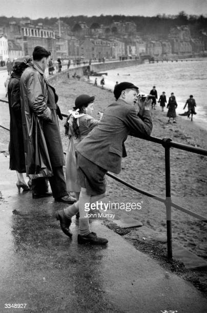 A boy using his pocketsized telescope to look out to sea from Rothesay promenade on the River Clyde Original Publication Picture Post 7761 Doon The...