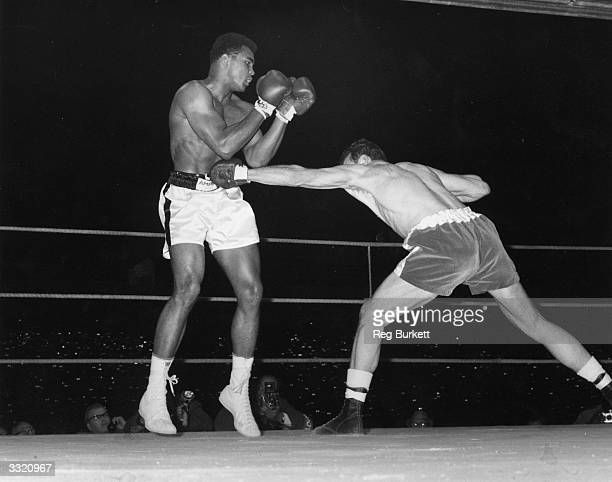 Henry Cooper lands a long reaching punch on Muhammad Ali during their World Heavyweight title fight at Arsenal's Highbury Stadium London Ali retained...