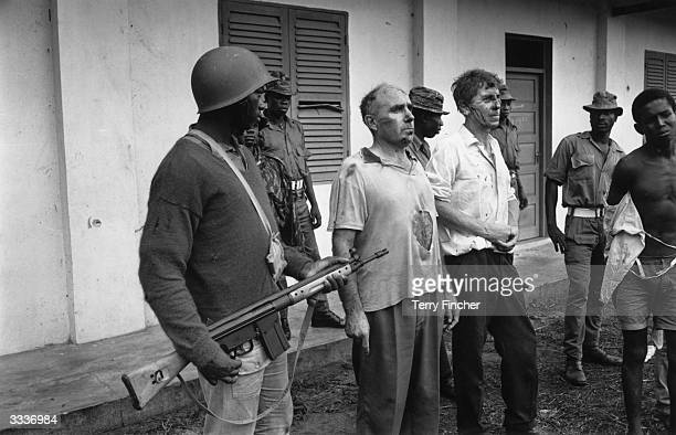 John DowningTractor a company rep and William Blakeley a marine manager under guard by Nigerian Federal troops who took them hostage when they...