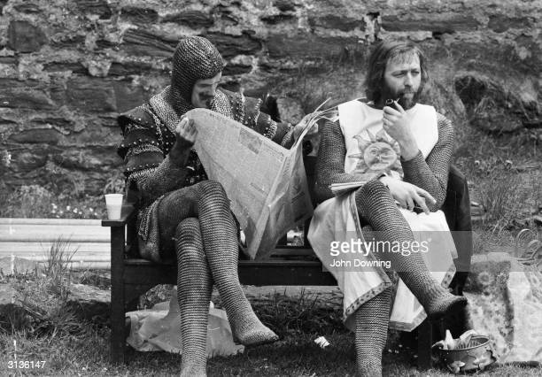 A chainmailclad John Cleese reads a newspaper while Graham Chapman smokes a quiet pipe on the set of 'Monty Python and the Holy Grail'