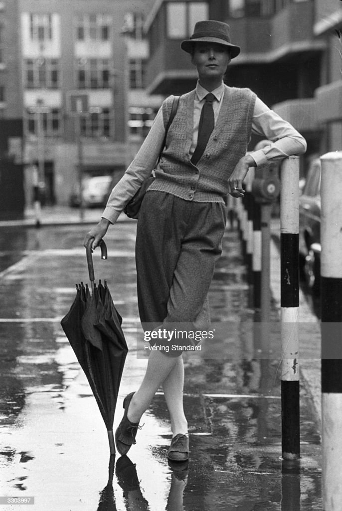 Cecile modelling a pair of grey flared knickerbockers, a waistcoat and hat in the rain. The clothes are from the Jaeger collection.