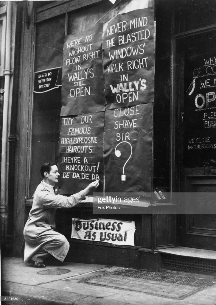 Wally's barber shop, St Martin Street has defiant signs outside after losing its windows during the London blitz.