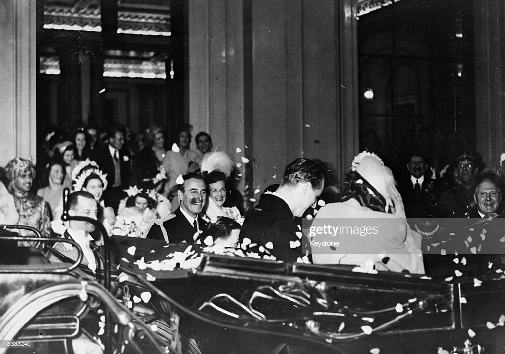 Princess Elizabeth and Prince Philip being showered with rose petals as they leave Buckingham Palace, London, for their honeymoon.