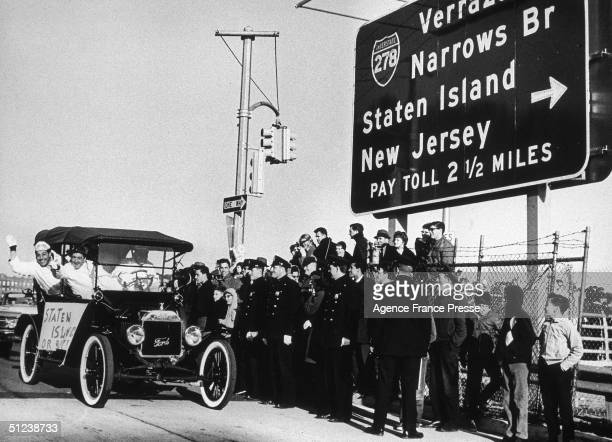 21st November 1964 An old car lurches across the line with cheering occupants at the opening of the Verrazano Bridge in New York City