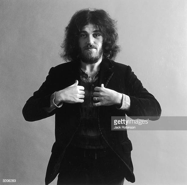Studio portrait of British rock singer Joe Cocker holding his hands at the lapels of his jacket