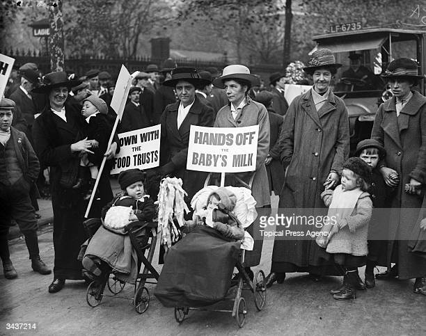 Women and children stage a protest against increased in milk prices and food trusts during World War I The signs read 'Hands off the Baby's Milk'