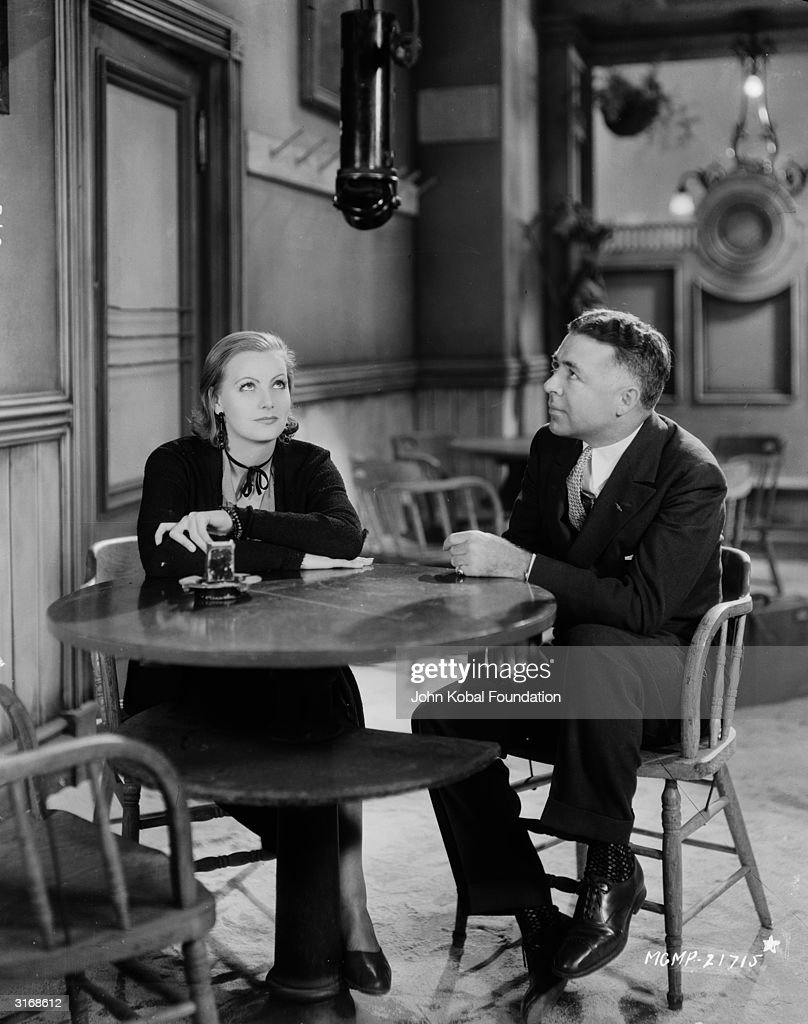 Swedish actress Greta Garbo (1905 - 1990) sitting with director Clarence Brown (1890 - 1987) on the set of the film 'Anna Christie'.