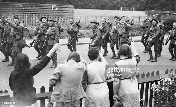 Women wave goodbye to troops 'somewhere in England' as they march off to WW II