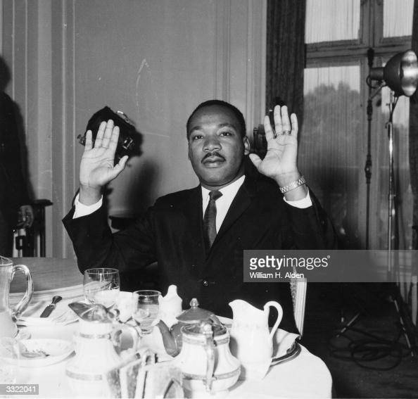 Black American civil rights leader and Baptist minister Dr Martin Luther King raising his hands in a restaurant