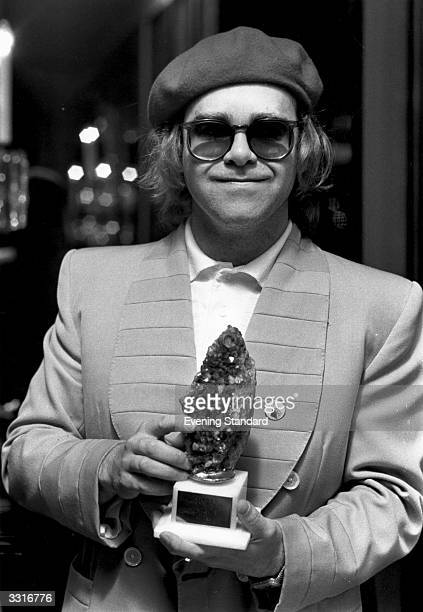 British pop star Elton John holding the Melody Maker trophy for Best Female Singer which he collected for Kiki Dee in her absence