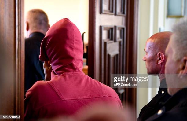 A 21yearold Dutchman is escorted in to court by officers for the first trial over violent riots against the G20 summit in Hamburg northern Germany on...