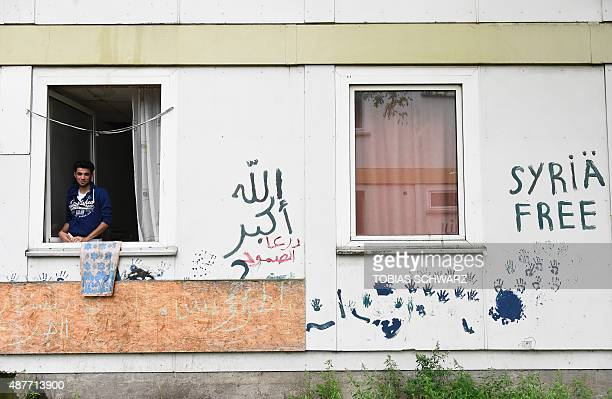 21years old Syrian refugee Abd Alrazak from Homs looks out of the window of his room at a temporary refugee home in Berlin's Spandau district on...