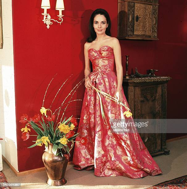 Schauspielerin DPorträt in einem roten Abendkleid und einer Narzisse in der Hand 1969