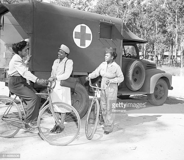 Second Lt Elena A Townsend of Glen Cove NY and Second Lt Inez E Holmes Norfolk VA stop for a moment in a bicycle tour of the camp to chat with 2nd Lt...