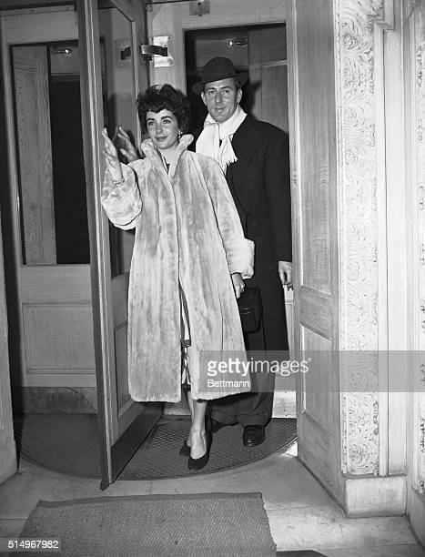 2/22/1952Michael Wilding and actress/wife Elizabeth Taylor are shown walking out of a buildings in a revolving door