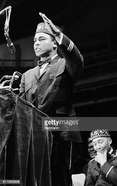 Black Muslim leader Elijah Muhammad Poole appears to be deep in thought and pleased with what he's hearing as Muhammad Ali addresses Black Muslim...