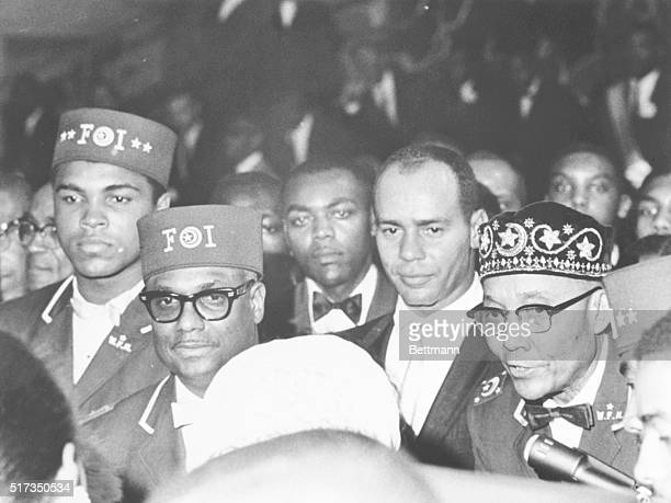 Black Muslim leader Elijah Muhammad leaves hall with disciples including heavyweight boxing champion Cassius Clay Clay sat in the front row of the...
