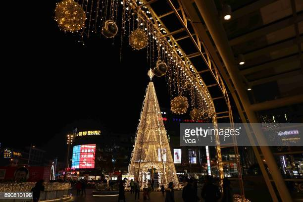 A 22metrehigh Christmas tree illuminates with golden LEDs to welcome Christmas at Qibao Ancient Town on December 11 2017 in Shanghai China Western...