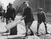 City boys enjoying a game of street cricket with a large homemade bat and a suitcase as the wicket