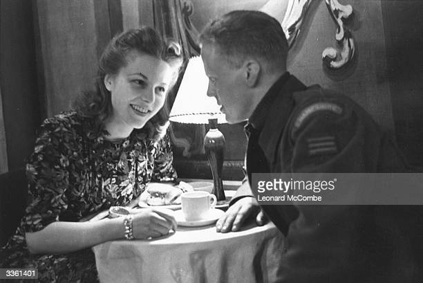 A soldier and a young woman talking over a coffee table in the Royal Opera House Covent Garden London Original Publication Picture Post 1680 Wartime...
