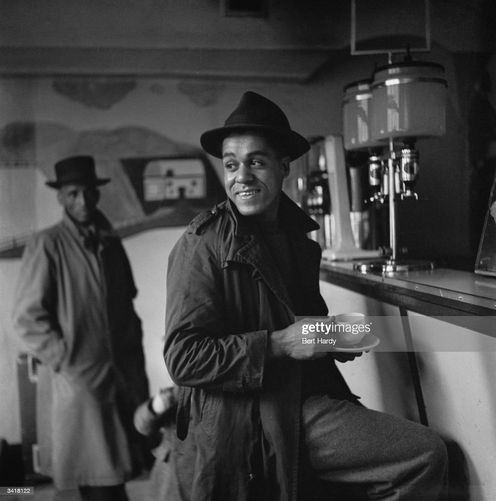 Drinking coffee in the dockland area of Cardiff, known as Bute Town or Tiger Bay. The district has a lively ethnic mix of people from many different origins, including Arab, Somali, West African, West Indian and Greek. Original Publication: Picture Post - 5020 - Down The Bay - pub. 1950