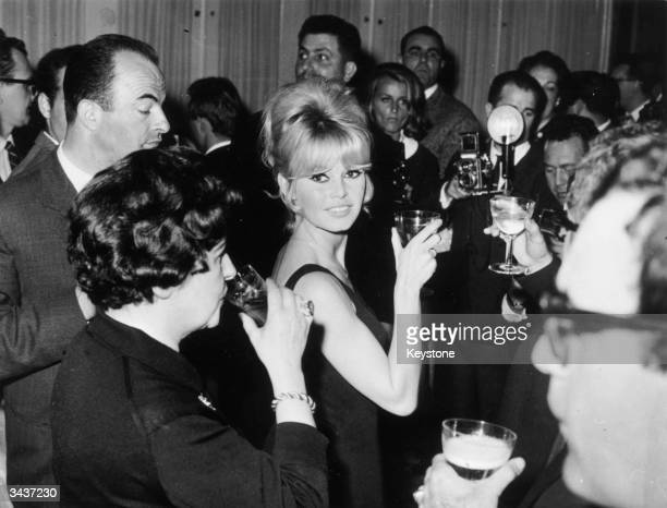 French film star Brigitte Bardot raises her glass at a press conference for JeanLuc Godard's latest film 'Le Mepris'