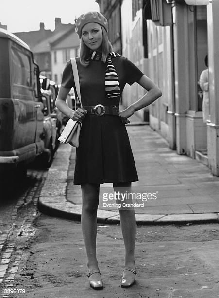 A woman models a mini dress and accessories in a London street