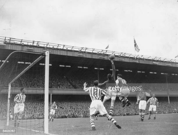 Arsenal winger Gerry Ward challenges the Huddersfield Town goalkeeper Wheeler for the ball during a match at Highbury London