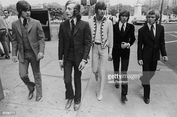 Australian pop/rock group the Bee Gees walk down the street in New York City The Gibb Brothers are flanked by drummer Colin Peterson and bassist...