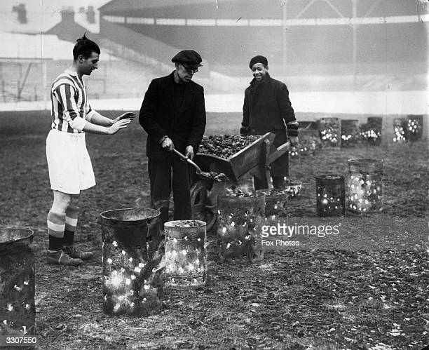 Ground staff at Stoke City tending the braziers which have been placed on the football pitch in an attempt to thaw the frozen ground Player Stanley...