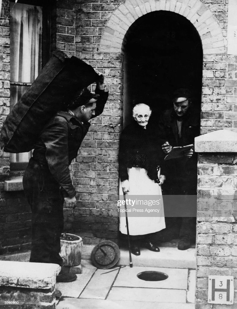 Mrs Pyke of Albany Road, Windsor watches as her annual gift from King George VI of coal which is delivered to the poor, is tipped from the hole in the front path to the cellar below.