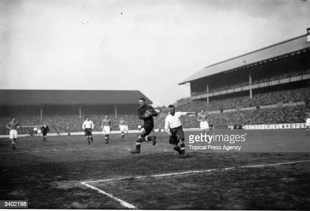 Everton's goalkeeper Sagan takes the ball ahead of Spurs' onrushing forward Meek as Tottenham Hotspur play Everton in an FA Cup tie replay at White...