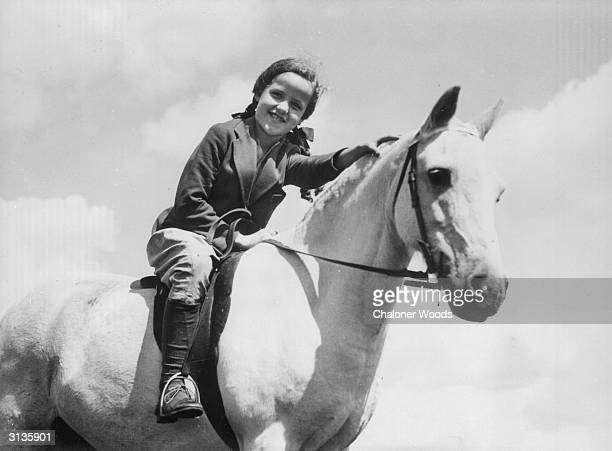 A little girl in ponytails leans forward to pat her steed's neck