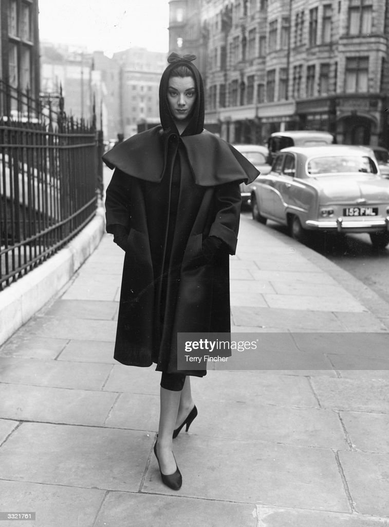 A fashion model wearing a dress and coat by Balenciaga during rehearsals for an appearance on the television show 'Fashions From Paris'