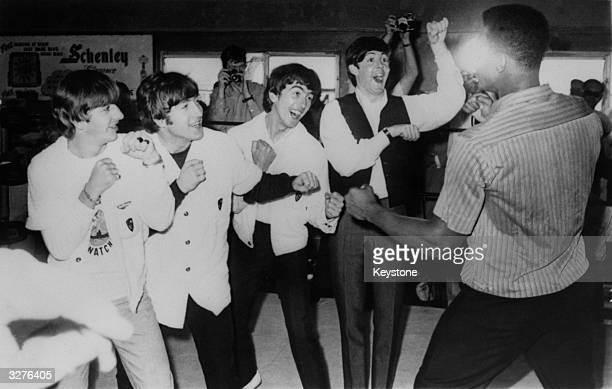 British pop group The Beatles from left to right Ringo Starr John Lennon George Harrison and Paul McCartney in the ring with champion American boxer...