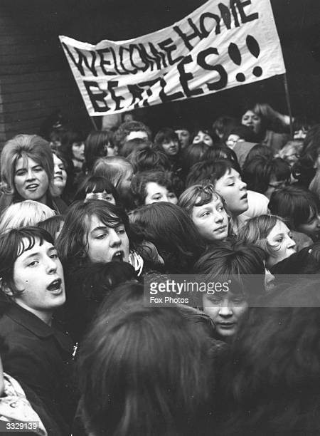 Fans of British pop group The Beatles waiting at London Airport with a banner to welcome them home from their tour of the United States