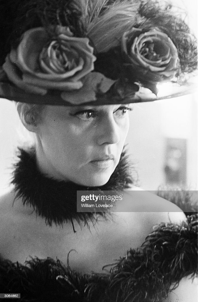 Jeanne Moreau ,in costume for her part in Viva Maria directed by Louis Malle, wears a flower decked hat and maribou feathers round her neck and shoulders.