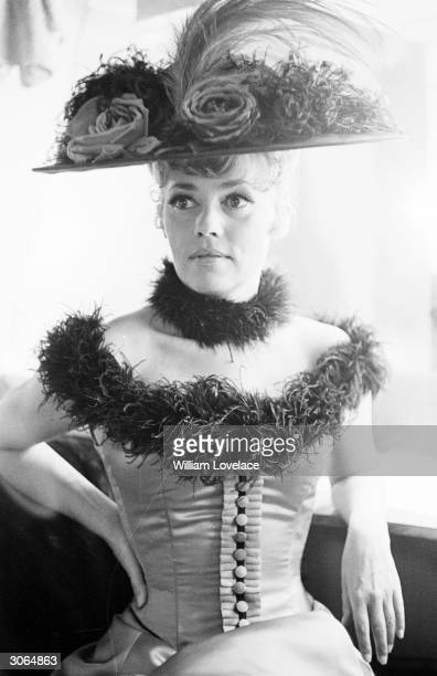 Jeanne Moreau in costume for her part in Viva Maria directed by Louis Malle wears a flower decked hat and maribou feathers round her neck and...