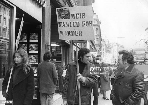 Peter Hain leader of Young Liberals heads a demo in a street outside El Al office holding poster 'Meir Wanted For Murder' after Israeli forces shot...