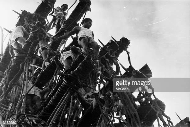 A group of young men prepare to perform a land dive from a bamboo platform during a visit by Queen Elizabeth and Prince Philip to Pentecost Island...