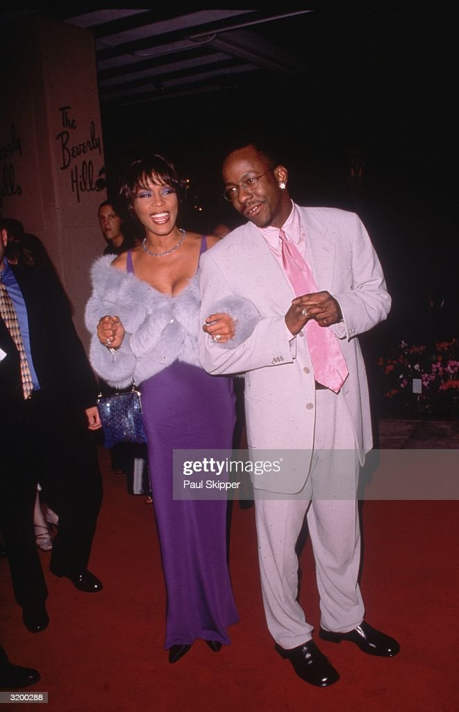 American singers Whitney Houston and husband Bobby Brown at the Arista Records Pre-Grammy party, held at the Beverly Hills Hotel, Beverly Hills, California. Houston was nominated for four Grammys and won Best Female R&B Vocal Performance for the song, 'It's Not Right But It's Okay,' which she performed at the awards ceremony. She wears a purple dress and fur wrap; Brown wears a white suit with a pink tie.