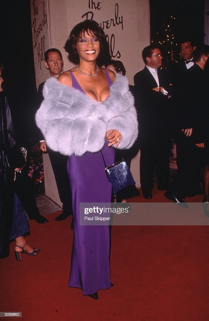 Full-length image of American singer Whitney Houston at the Arista Records Pre-Grammy party, held at the Beverly Hills Hotel, Beverly Hills, California. Houston received four Grammy nominations, winning Best Female R&B Vocal Performance, and also performed at the awards ceremony. She is wearing a purple gown with a fur wrap.