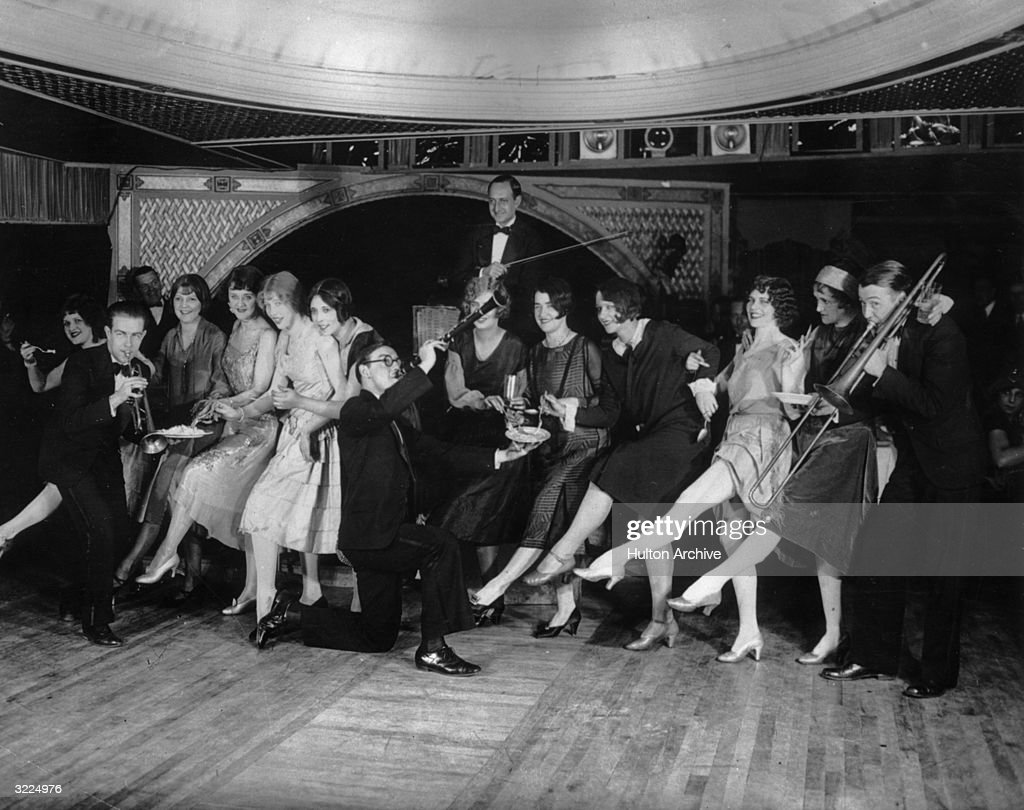 Female flappers kicking dancing and having fun while musicians perform during a Charleston dance contest at the Parody Club