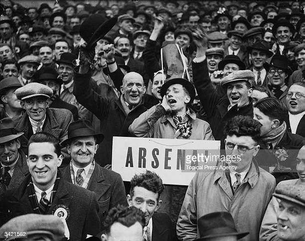 An Arsenal football club supporter declares his allegiance with a large sign during a match against Wolverhampton Wanderers