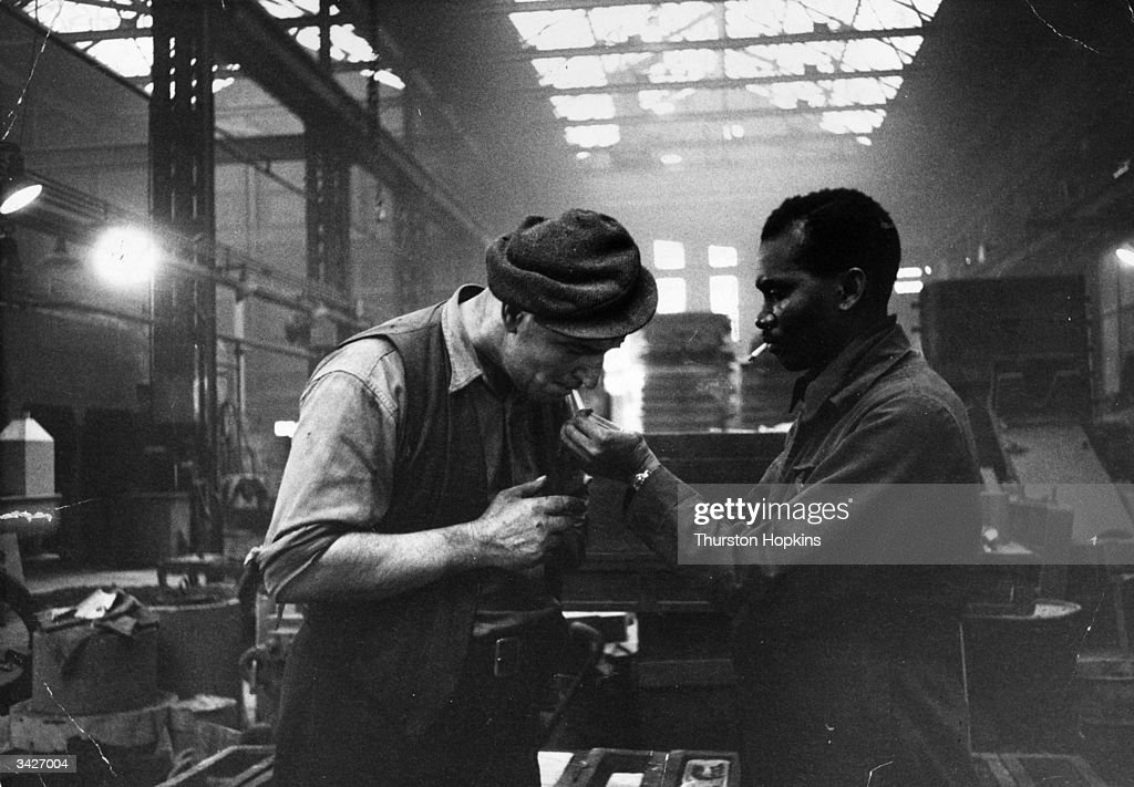 Jamaican immigrant Kwessi Blankson gives a light to workmate Jack White at The Phosphor Bronze Company where he is in charge of the oil-burners. Original Publication: Picture Post - 7482 - A British Colour Conflict - pub. 1955