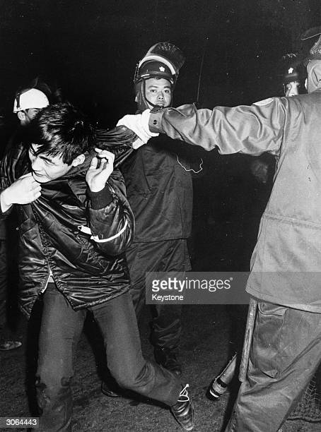 A Zengakuren student is arrested by riot police during a demonstration in Tokyo against the visit to Sasebo of the United States nuclear powered...
