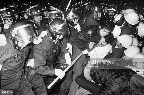 A student is arrested by riot police during a demonstration in Tokyo against the visit to Sasebo of the United States nuclear powered aircraft...